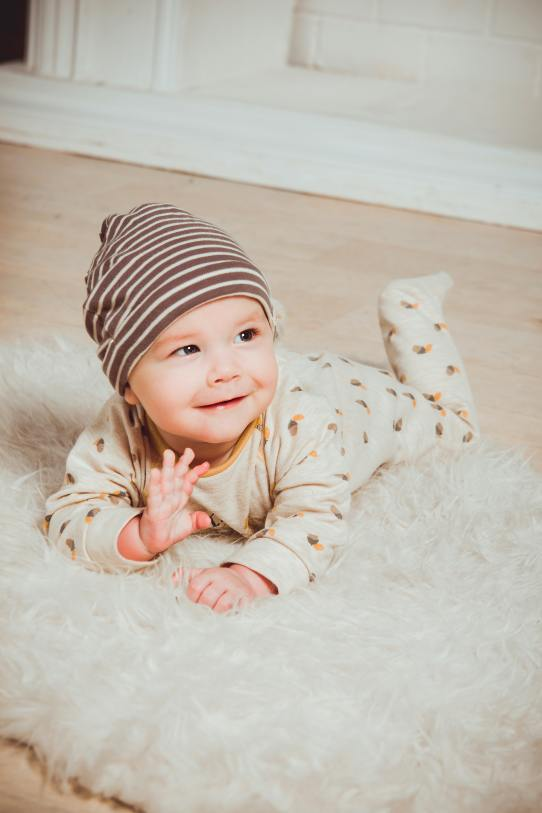 smiling-baby-lying-on-white-mat-1648377