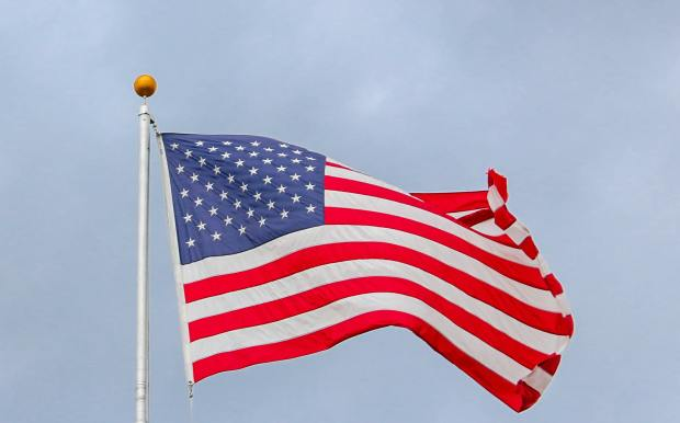 usa-flag-waving-on-white-metal-pole-1550342